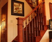 Custom maple staircase with box newels with turned wooden balusters and return miter treads